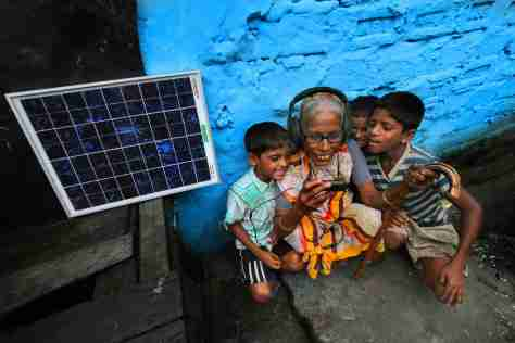 A solar PV panel powers an electronic device entertaining an elderly woman and children in West Bengal, India. Supriya Biswas