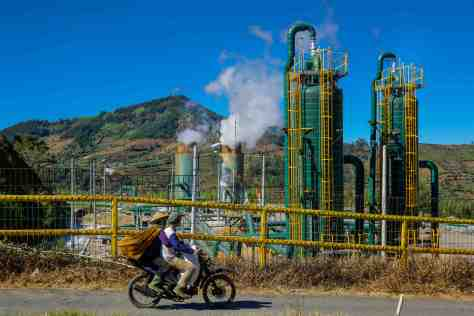 A motorcyclist and his passenger watch steam rise out of the Dieng Plateau's geothermal power plant in Java, Indonesia. Bambang Wirawan