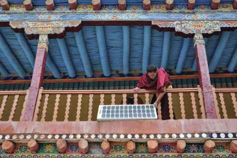 A monk positions a solar PV panel at the remote Hemis Monastery in Ladakh, India. Debdatta Chakraborty